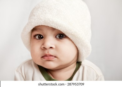 Adorable indian baby boy in white cap looking at camera over gray background
