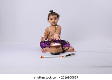 adorable Indian baby in krishna kanha or kanhaiya dress posing with his flute and dahi handi (pot with curd) on white background. sitting pose