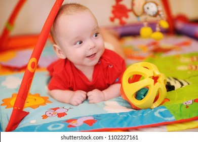 Adorable infant lying on colorful baby play mat with toys. Child early development and activity space. Tummy time fun