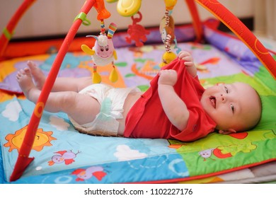 Adorable infant lying on colorful baby play mat with toys. Child early development and activity space