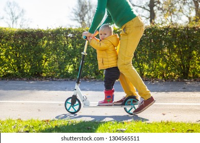 Adorable infant son riding on scooter in public playground, Zagreb, Croatia.