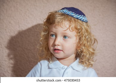 Adorable Jewish child in a blue yarmulke - skullcap. Little boy with long blond curls and blue eyes