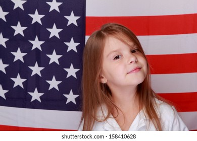 Adorable joyful little girl with long hair and a beautiful smile on the background of the flag of the United States