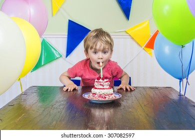 Adorable kid blowing out the candle on his birthday cake