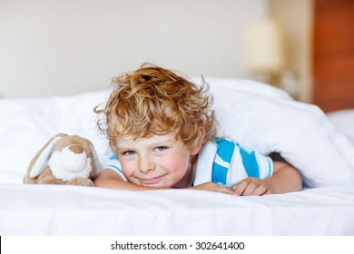 Adorable kid boy after sleeping in his white bed with toy. Little happy child playing with toy bunny.