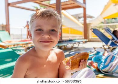 Adorable kid boy eating hot dog at the beach aquapark