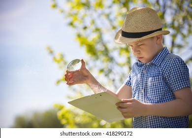 Adorable kid boy making fire on paper with a magnifying glass outdoors, on sunny day. Child exploring fire nature in the garden. Young explorer with magnifier. Education and discovery concept
