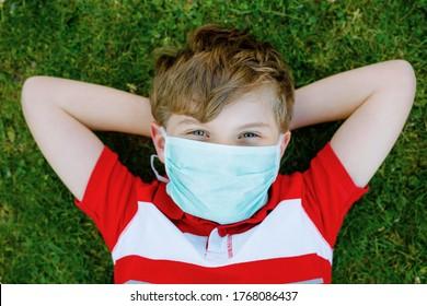 Niño Adorable con mascarilla médica como protección contra la enfermedad de cuarentena del coronavirus pandémico. Niños en edad escolar que utilizan equipos de protección como lucha contra el cóvido 19.