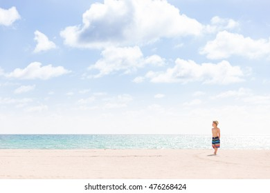 Adorable kid boy standing on the sandy beach by the ocean and looking on the gorgeous summer view. Miami summer vacations. Blue sky with clouds as a background. Child on the  amazing beach.