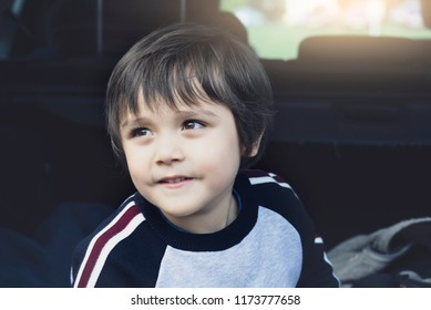 Adorable kid boy wearing warm clothes sitting in car trunk,Happy child playing in open car boot with happy face while waiting for parent get ready for vocation,Family trip traveling by car concept