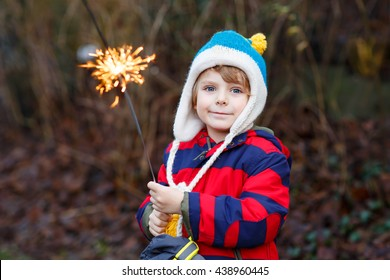 Adorable kid boy in winter clothes holding burning sparkler on New Year's Eve. Safe fireworks for kids concept. Happy child having fun outdoors.