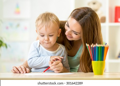 adorable kid child boy drawing with mother help
