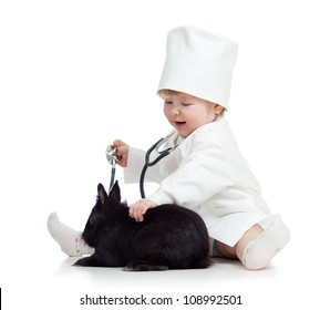 Adorable kid with clothes of doctor. Girl is playing with pet bunny
