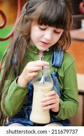 Adorable kid girl drinking milk coctail outdoors in the garden