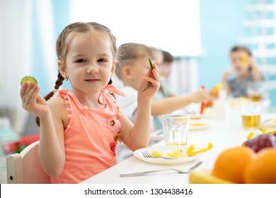 Adorable kid girl eating vegetables in kindergarten