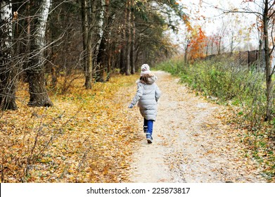 Adorable kid girl in grey coat hat and scarf walking in the fall forest with first snow