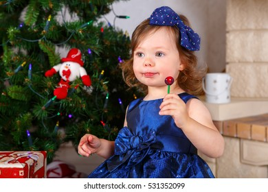 Adorable kid girl playing with Christmas tree decoration. Toddler girl with gifts for xmas. Near fireplace at home. Traditional family holiday. Happy child celebrating Christmas.
