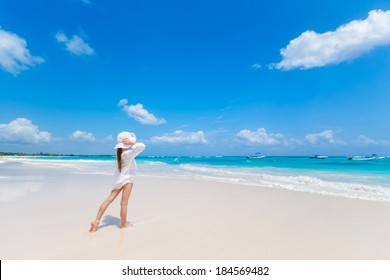 Adorable kid girl in white dress and hat staying ob beach and looking at Caribbean sea