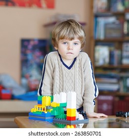 Adorable kid playing with lots of colorful plastic blocks indoor. Child having fun with building and creating.
