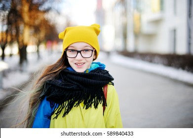 Adorable kid pre teen girl in yellow hat and glasses on shopping