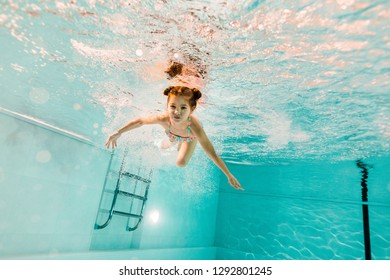 adorable kid swimming underwater in clear water in swimming pool