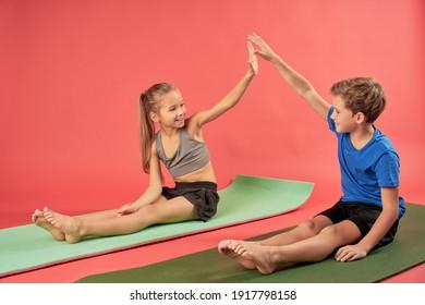 Adorable kids sitting on yoga mats and giving high five