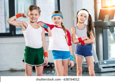 adorable kids in sportswear smiling and posing at fitness studio, children sport concept