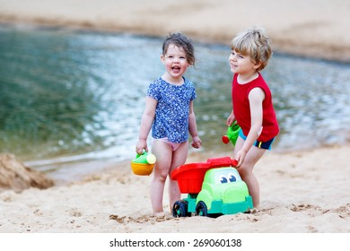 Adorable kids, two siblings, girl and boy having fun and playing together with sand toys near city lake on hot summer day. Active outdoors leisure with kids in summer, on sunny ay.