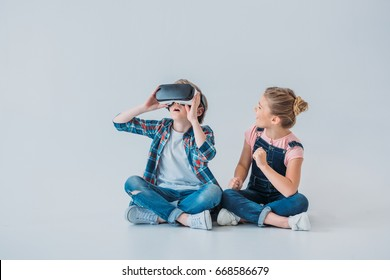 adorable kids using virtual reality headset while sitting on the floor