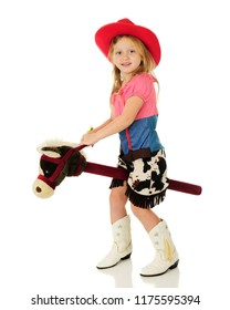 An adorable kindergarten cowgirl happily riding a stick horse while looking at viewer. Isolated on white.