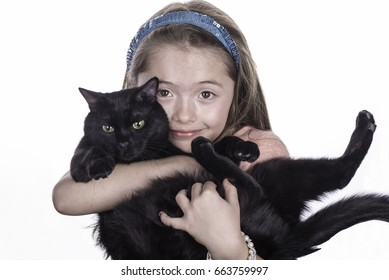 Adorable kitten being held by the young girl that picked him out.