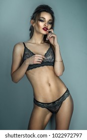 adorable lady with red lips and beautiful hairstyle posing on camera in grey lace lingerie in studio