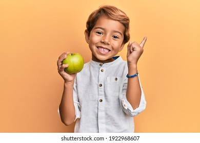 Adorable latin kid holding green apple smiling happy pointing with hand and finger to the side
