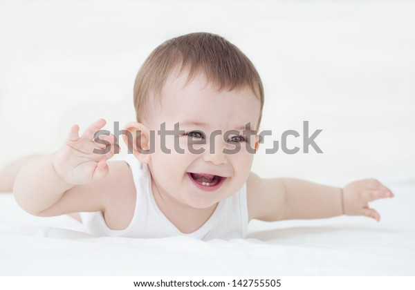Adorable laughing baby boy showing his first teeth