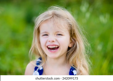 Adorable laughing little girl with long blond curly hair, outdoor portrait in summer park on bright sunny day. Smiling child in green grass field. Closeup portrait.