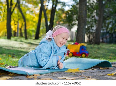 Adorable laughing little girl playing in the park lying on her stomach on a mat