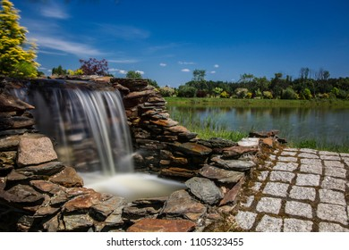 adorable ling exposure little waterfall, small lake behind and crystal blue sky