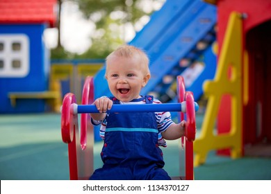 Adorable little 1-2 year old toddler boy having fun on playground, child playing with different activities