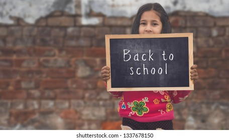 Adorable little 6-8 years old Asian girl smiling, holding back to school chalkboard.