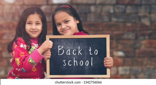 Adorable little 6-8 years old and 8-10 years old Asian girls smiling, holding back to school chalkboard.