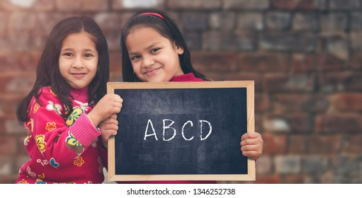 Adorable little 6-8 years old and 8-10 years old Indian girls smiling, holding education chalkboard.