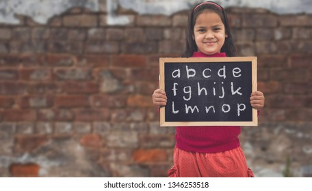 Adorable little 8-10 years old Indian Asian girls smiling, holding education chalkboard.