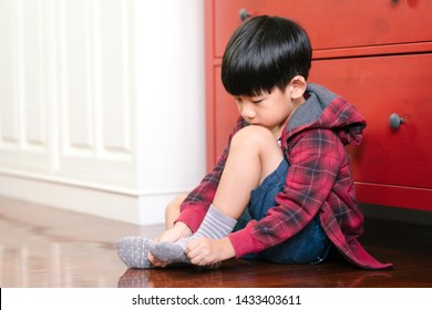 An adorable little asian boy putting on socks, getting ready for school. Montessori practical life skills, Self-care, Child development, Fine motor, Hand eye coordination, Kids daily routine concept.