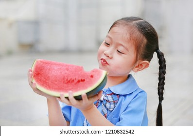 Adorable little Asian child girl in school uniform enjoy eating watermelon.