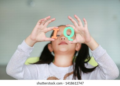 Adorable little Asian child girl holding alphabet IQ (Intelligence Quotient) text on her face. Education and development concept.
