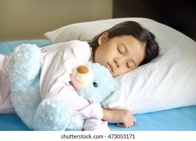 Adorable little Asian girl with black hair sleeping in the bed with her toy. The child girl hugs the blue teddy bear.