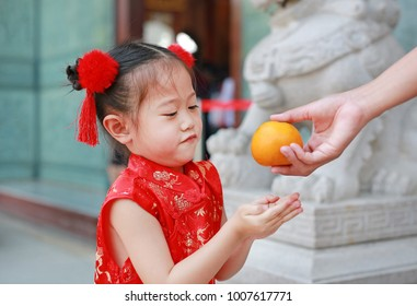 Adorable little Asian girl getting sacred Orange at chinese temple in bangkok thailand, Chinese new year concept.