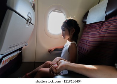 Adorable little Asian girl traveling by an airplane. Child sitting by aircraft window and holding her mother hands during airplane take off the flight.