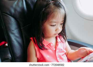 Adorable little asian girl traveling by an airplane.Girl sitting by aircraft window and reading her book during the flight. Traveling abroad with kids.