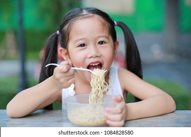 Adorable little Asian kid girl eating Instant noodles in the morning at the garden.